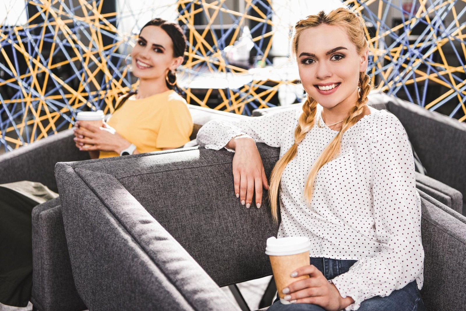 Young women having coffee in a modern office space.